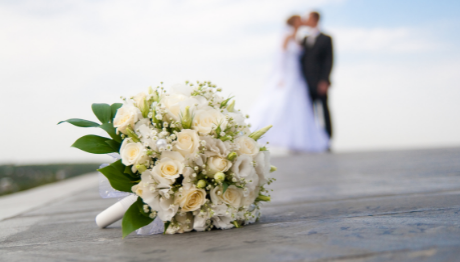 Wedding flowers with couple in background paid for with AFFCU HELOC