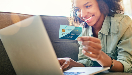 Young lady on sofa ordering online with AFFCU credit card