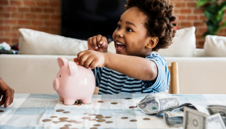 AFFCU Journey Savings Account Young boy smiling outting coins in piggy bank