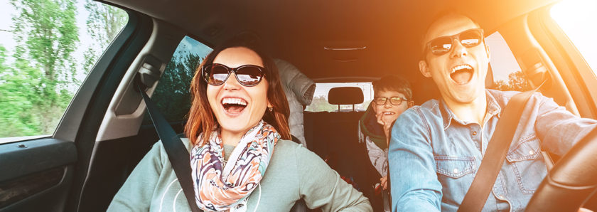 Smiling family in car on sunny day