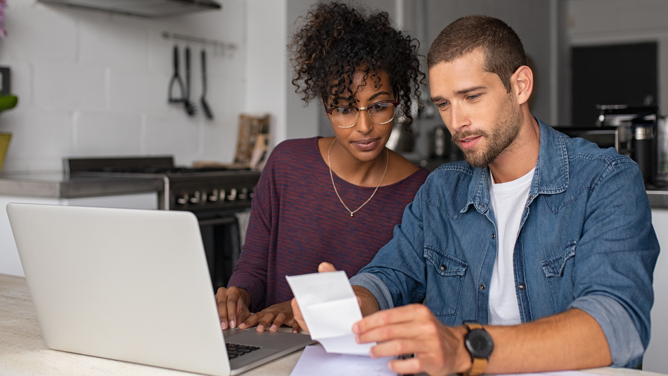 Fall financial checkup blog cover banner - Young couple sitting at table with laptop reviewing budget
