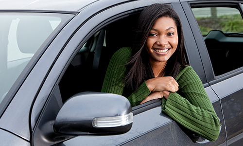 Young girl in car window smiling as a new driver