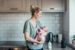 AFFCU Voice Banking - MOther holding baby in kitchen using voice assistant speaker
