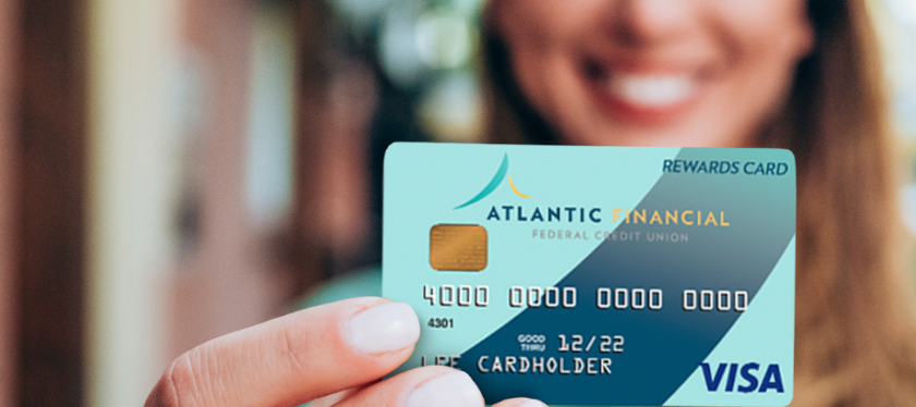 AFFCU Visa Platinum Rewards Credit Card - Card held in hand extended out in fromt of smiling woman