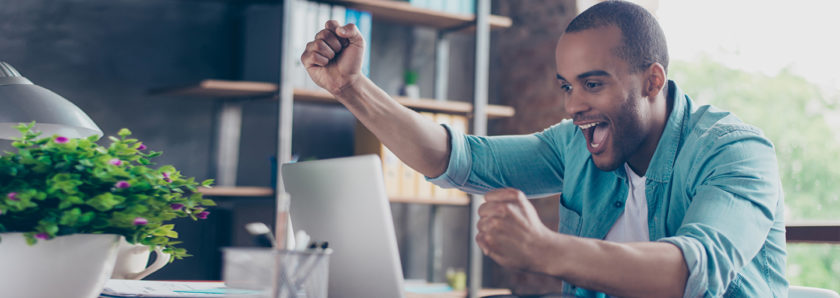 Man throwing hands in the air with excitement while viewing account online at laptop