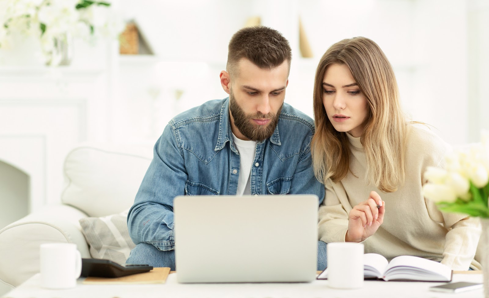 couple reading about how to open a checking account online at home computer