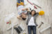 Smiling young couple laying on floor with construction items of home remodel