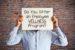 man holding sign over face asking do you offer employee wellness program