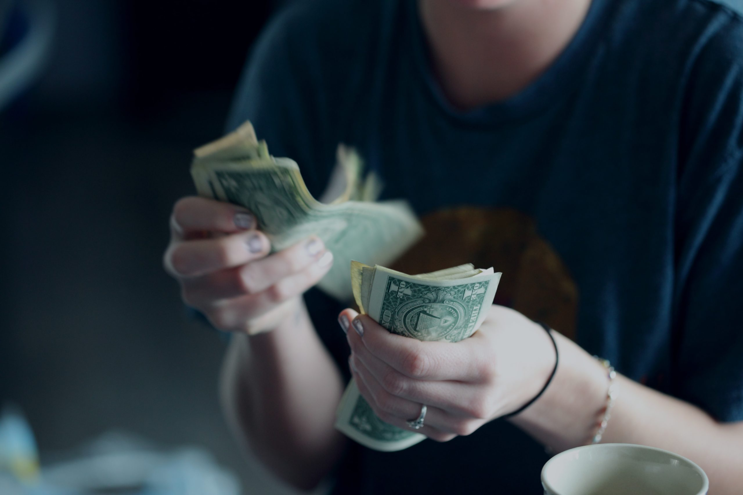 Womans hands counting dollar bills